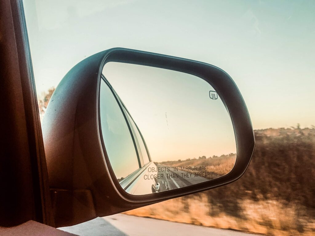 Side mirror of car during sunset